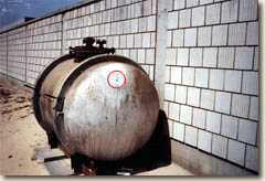 Storage tank found at the Kuwaiti Girls School. Rust-colored fumes eminate from a buleet hole inside the red circle.